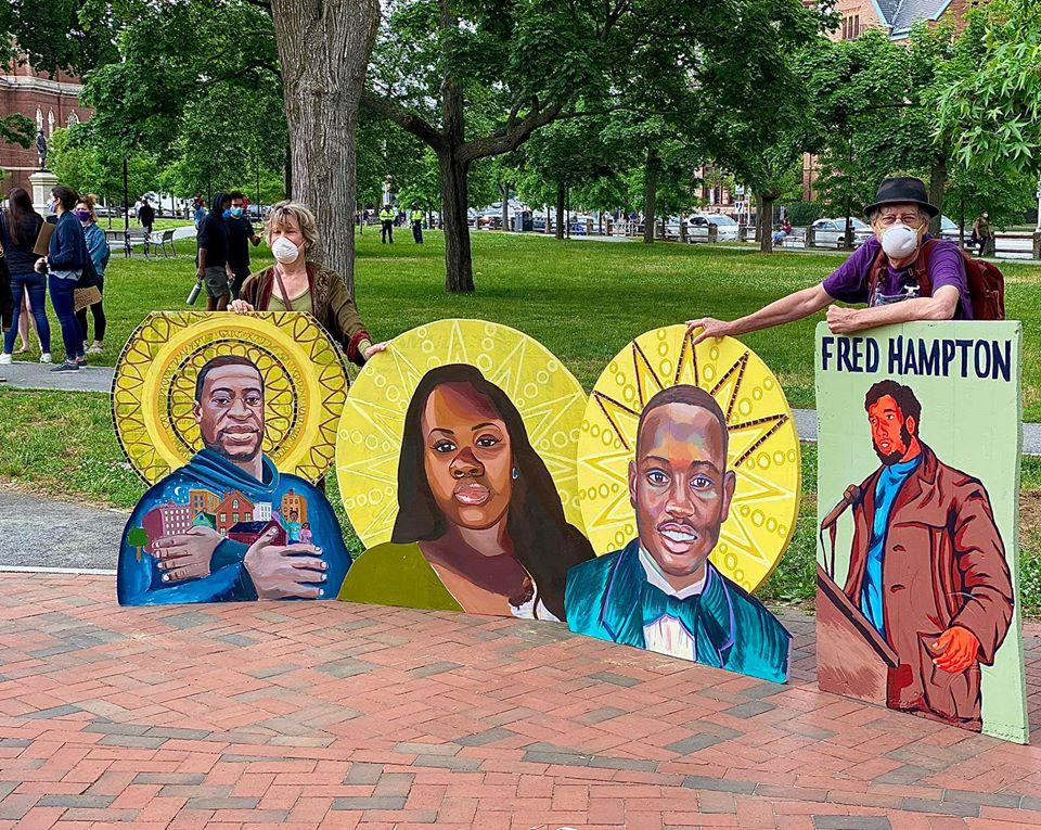 Protest art from David Fichter, right (muralist) pictured here with wife Debra Wise, (left), Artistic Director, Underground Railway Theater. The images portray unarmed Black victims of police murder: L–R, George Floyd; Breonna Taylor; Ahmaud Arbery, 2020; and Fred Hampton, 1969. —photo by Marina Boni